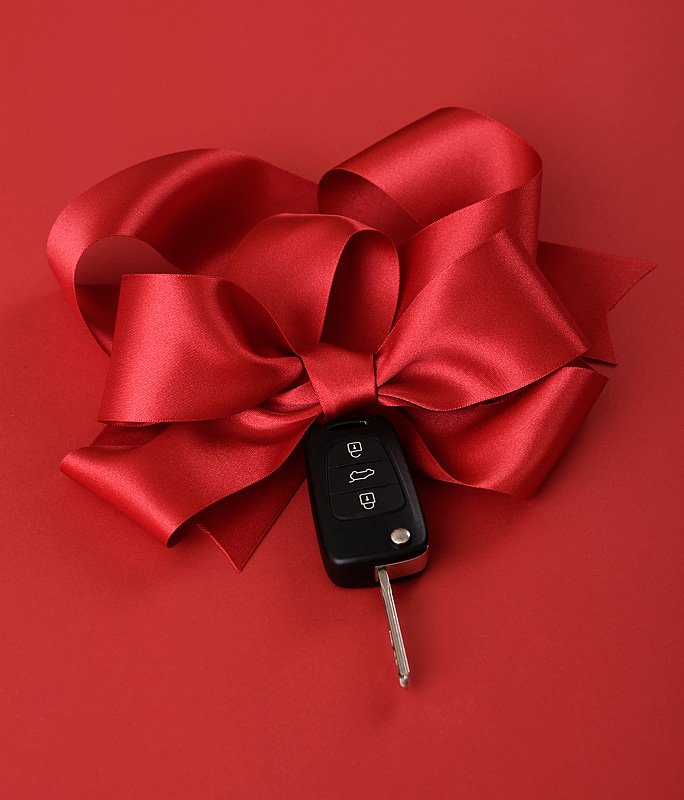 Red Bow and Car Key on Red Background